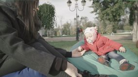 Mother and her little daughter in outdoors. Mom holds the baby`s hand stock video footage