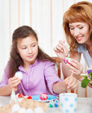 Mother and her little daughter painting on Easter eggs Stock Photos