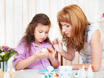 Mother and her little daughter painting on Easter eggs Royalty Free Stock Images