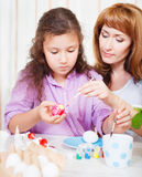 Mother and her little daughter painting on Easter eggs Royalty Free Stock Photography