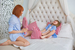 Mother with her little daughter play a pillows on a bed. Mother with her little daughter play a pillows on bed Stock Photography