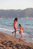 Mother and her little daughter playing and running on the beach Stock Photo