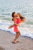 Mother and her little daughter playing and running on the beach Royalty Free Stock Image