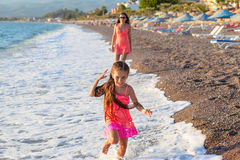 Mother and her little daughter playing and running on the beach Stock Image