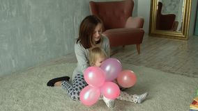 Mother and her little daughter plays with balloons stock video