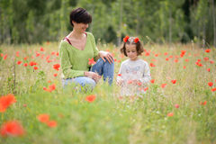Mother with her little daughter in poppy field Stock Images