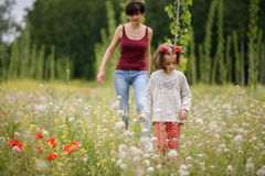 Mother with her little daughter in poppy field Royalty Free Stock Photos