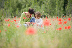Mother with her little daughter in poppy field Royalty Free Stock Photography