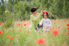 Mother with her little daughter in poppy field Stock Photos