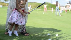Mother and her little daughter practicing to hit the ball stock video