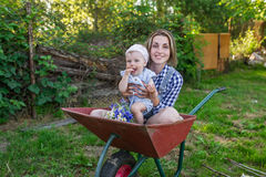 Mother and her little daughter sit in the wheelbarrow outdoors Royalty Free Stock Photos