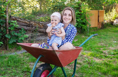 Mother and her little daughter sit in the wheelbarrow outdoors Stock Image