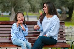 Mother and her little daughter sitting on a bench eating a cookie stock photo