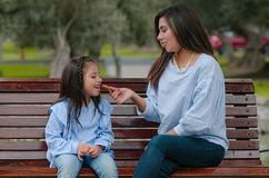 Mother and her little daughter sitting on a bench eating a cookie stock photography