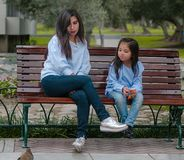 Mother and her little daughter sitting on a bench royalty free stock image