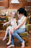 Mother and her little daughter sitting in a chair. At home Royalty Free Stock Images