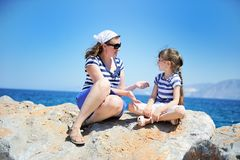 Mother and her little daughter sitting on rocks Royalty Free Stock Image