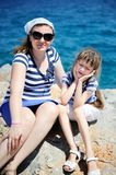 Mother and her little daughter sitting on rocks Stock Images