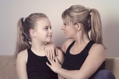 Mother and her little daughter sitting on the sofa and looking at each other. Mother and her little daughter sitting on the sofa and looking at each other royalty free stock photography