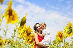 Mother and her little daughter in the sunflower field royalty free stock photo