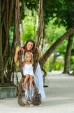Mother and her little daughter in tropical park Royalty Free Stock Image