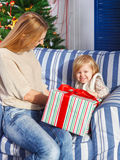 Mother with her little daughter under the Christmas tree Royalty Free Stock Images