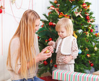 Mother with her little daughter under the Christmas tree Stock Images