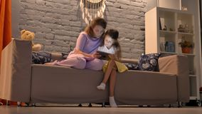 Mother and her little daughter using tablet, sitting together on couch in living modern room, family concept with gadget stock video footage