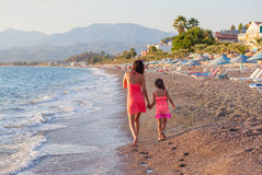 Mother and her little daughter walking along the beach Stock Photography
