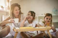 Mother with her little daughters having breakfast in the bed. Royalty Free Stock Photo