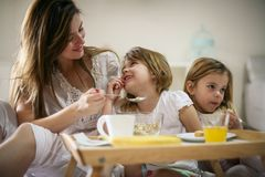 Mother with her little daughters having breakfast in the bed. stock photography