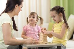 Mother and her daughters playing in board game. Mother and her little daughters playing in board game royalty free stock image