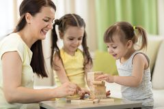 Mother and her daughters playing in board game. Mother and her little daughters playing in board game Royalty Free Stock Photo