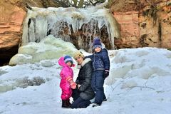 Mother with her little daughters posing near frozen waterfall, winter Royalty Free Stock Images