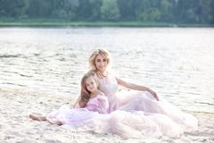 Mother and her little girl enjoying lake view and relaxing on the beach on a sunny day in beautiful dresses. Family lifestyle and. Mother and her little girl stock photography