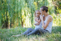 Mother and her little girl on green summer grass meadow having fun. Sporty mother and daughter having fun after yoga exercise outdoor Stock Image