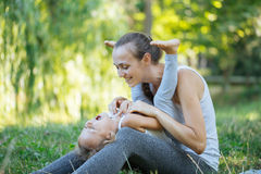 Mother and her little girl on green summer grass meadow having fun. Sporty mother and daughter having fun after yoga exercise outdoor Royalty Free Stock Photo