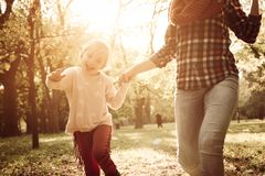 Mother and her little girl holding hands and running trou stock images