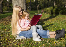 Mother and her little girl reading book Stock Image