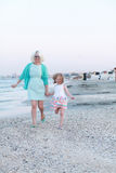 Mother and her little girl running on the seashore. Stock Photography