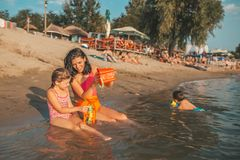 Mother and her little happy daughter are playing with beach toys in the water royalty free stock images