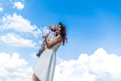 Mother with her little son on the blue sky behind Royalty Free Stock Images