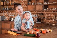 Mother with her little son cooking dinner together and using digital tablet in the kitchen Royalty Free Stock Photos