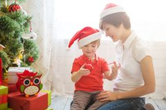 Mother with her Little son decorating christmas tree at home. Family preparing home for xmas celebration.  stock photo