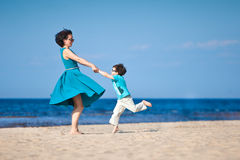 Mother and her little son playing on the beach Stock Images