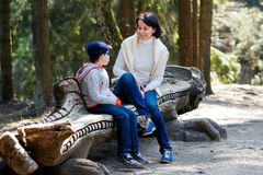 Mother and her little son sitting on a bench Royalty Free Stock Photography