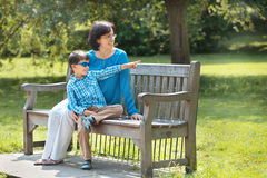 Mother and her little son sitting on a bench Stock Photo
