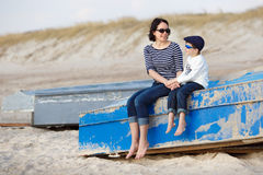 Mother and her little son sitting on a boat Stock Photos