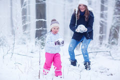 Mother and her little toddler daughter playing with snow balls Stock Image