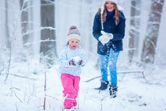 Mother and her little toddler daughter playing with snow balls Royalty Free Stock Photos